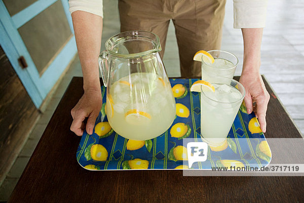 Mature woman with tray of lemonade
