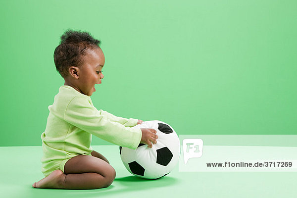 Baby Junge spielt mit Fußball