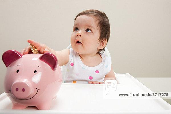 Junge im Hochstuhl sitzend mit Sparschwein und Münzen