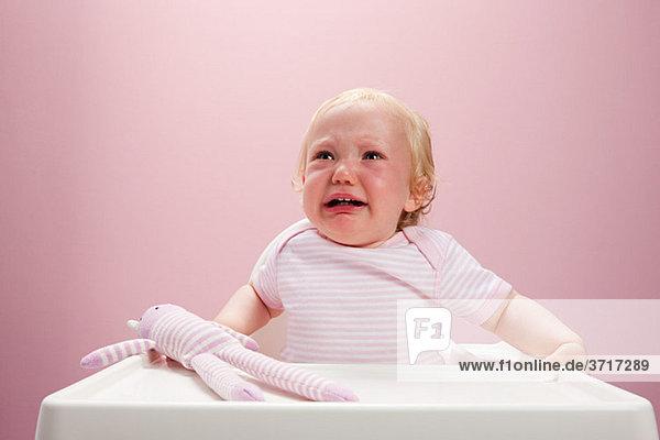 Kleines Mädchen im Hochstuhl sitzend weinend