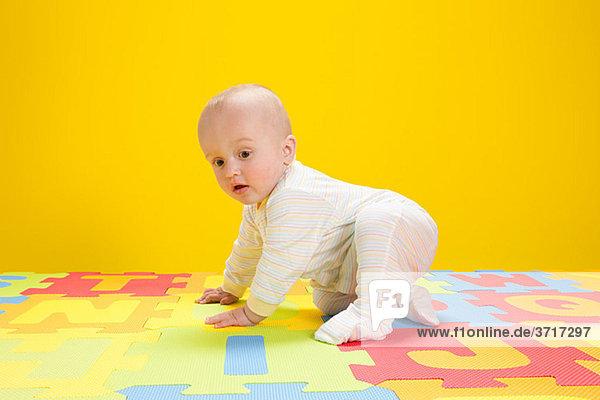 Baby Junge spielt mit Spielzeugalphabetbuchstaben