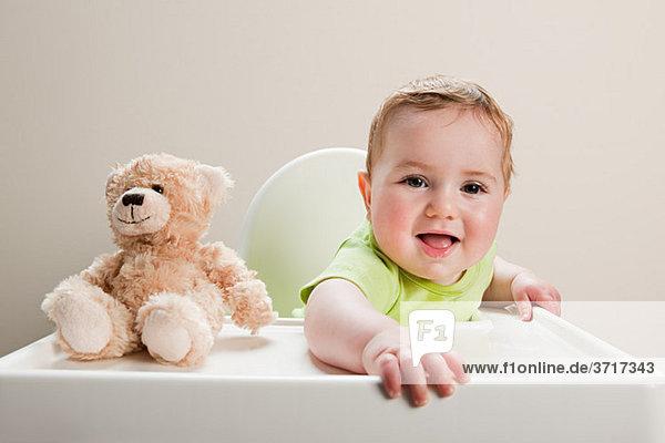 Junge im Hochstuhl sitzend mit Teddybär
