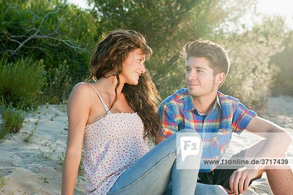 Junges paar sitzen auf sand