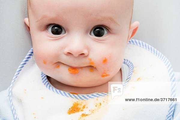Baby mit Essen im Gesicht