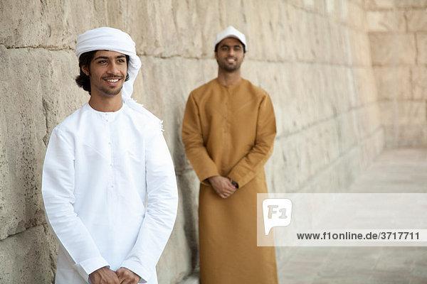 Männer aus dem Nahen Osten  die von einer Steinmauer angeschaut werden.