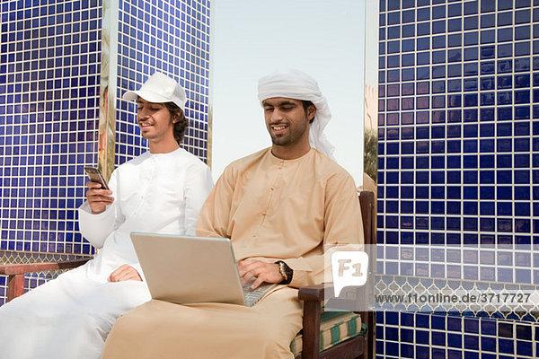 Zwei Männer aus dem Nahen Osten mit Laptop und Handy