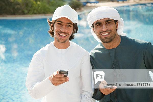 Zwei Männer aus dem Nahen Osten mit Mobiltelefonen