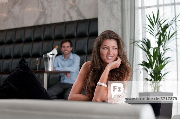 Junge Frau am Tisch mit Mann im Hintergrund