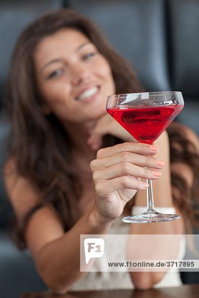 Toasts der jungen Dame mit einem Cocktail