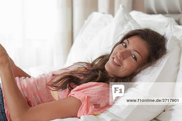 Junge Frau im Bett liegend