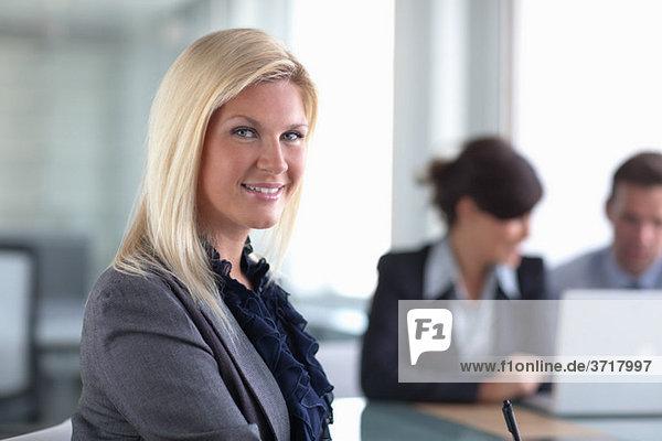Geschäftsfrau und Kollegen am Laptop