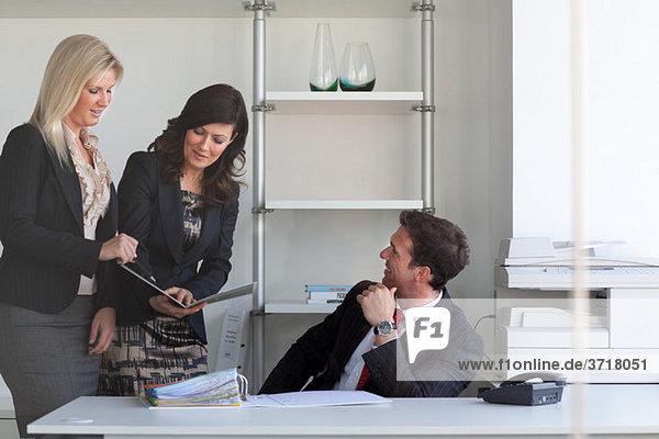 Geschäftsfrauen im Gespräch mit Geschäftsmann am Schreibtisch