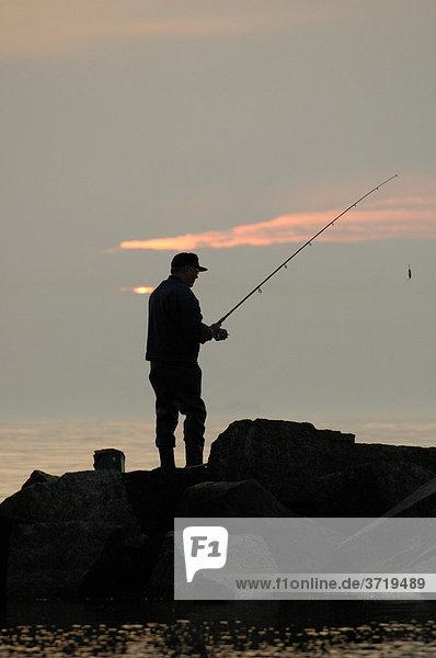 Ein Angler steht im Abendlicht am Ufer der Ostsee