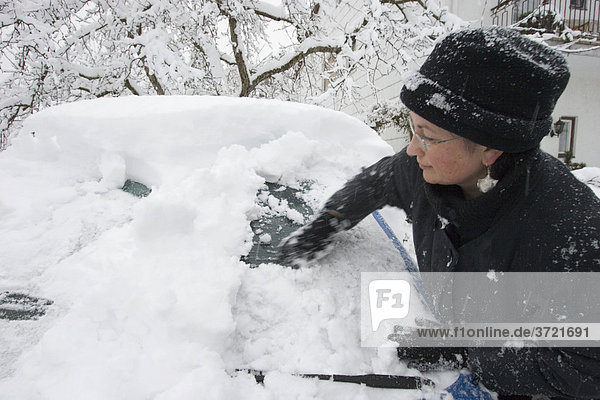 Eingeschneites Auto Opel Corsa blau - Frau beseitigt Schnee vom Auto
