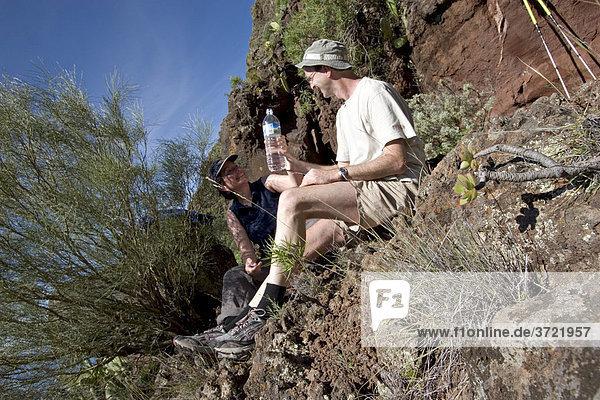 Paar trinkt Wasser aus Plastikflasche Valle Gran Rey La Gomera Kanaren
