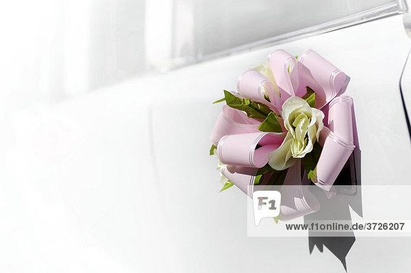 Blumen mit einer rosa Schleife an der Tür einer weißen Hochzeits-Limousine