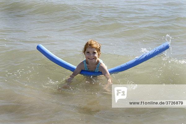 Mädchen schwimmt mit Schwimmhilfe  Schwimmschlange  im Meer