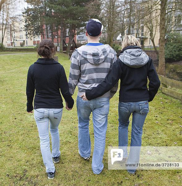 Drei Teenager  Rückenansicht  unentschlossene Jugend beim Spaziergang