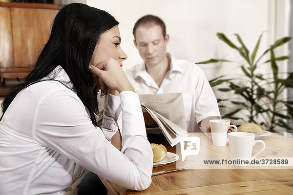 Junge Frau sitzt gelangweilt am Frühstückstisch während er die Zeitung liest