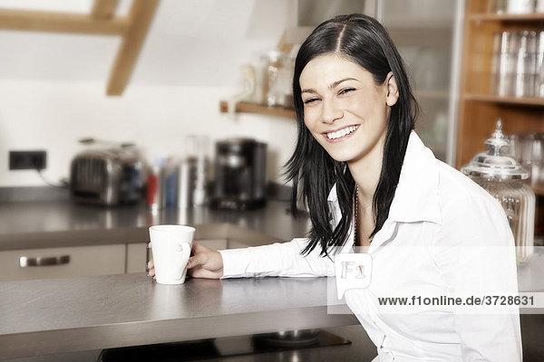 Junge Frau trinkt Kaffee  mit Blick zum Betrachter  Portait
