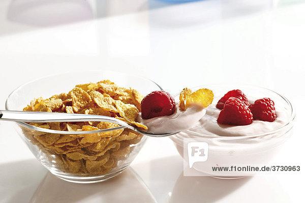 Cornflakes und Himbeerjoghurt in Glasschälchen und ein Löffel Himbeerjoghurt mit Cornflakes