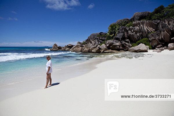 Eine Frau steht am Strand von Grand Anse mit den typischen Granitfelsen von La Digue  Indischer Ozean  Insel La Digue  Seychellen  Indischer Ozean  Afrika