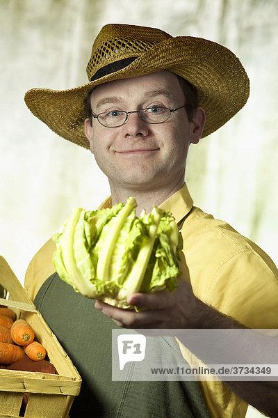 Gemüsehändler  Portrait eines Mannes mit Strohhut und Korb mit Gemüse