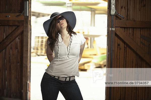 Junge Frau mit Hut in Jeans  Sonnenbrille und weißer Bluse in Fabrikhalle