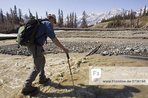 Wanderer überquert den Sheep Creek Fluss und stützt sich mit Wanderstöcken ab  Slims River Valley Flusstal  Kluane Nationalpark  Yukon Territory  Kanada