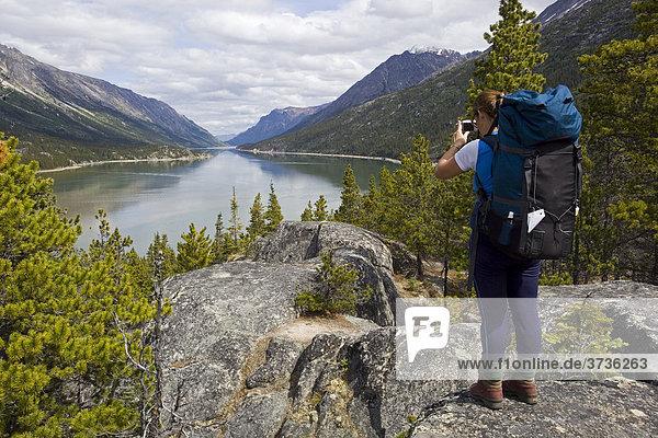 Wandererin  Rucksackreisende macht Fotos vom Bennett See  Chilkoot Pass  Chilkoot Trail  Yukon  Britisch-Kolumbien  Kanada