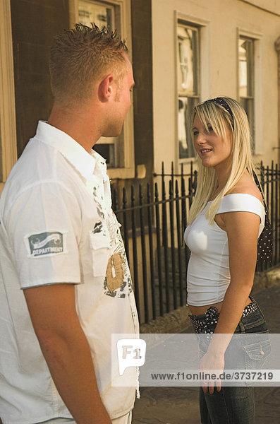 Junger Mann dreht sich nach einer attraktiven jungen Frau um  die auf der Straße an ihm vorbeigeht