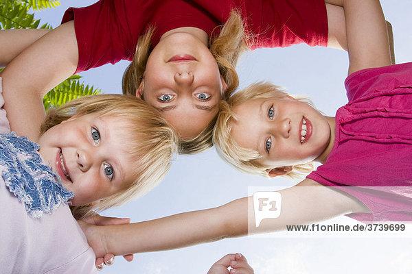 Drei Schwestern  3  13 und 7  umarmen sich und blicken nach unten in die Kamera