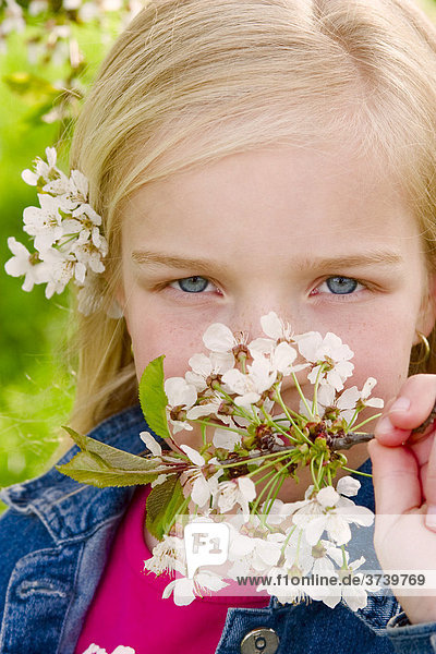 Blondes Mädchen mit Blüte im Haar und in der Hand  Portrait