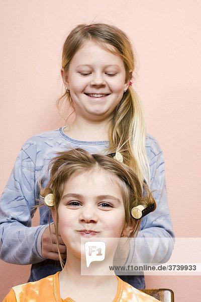 Zwei Mädchen  11 und 6 Jahre  spielen Friseur