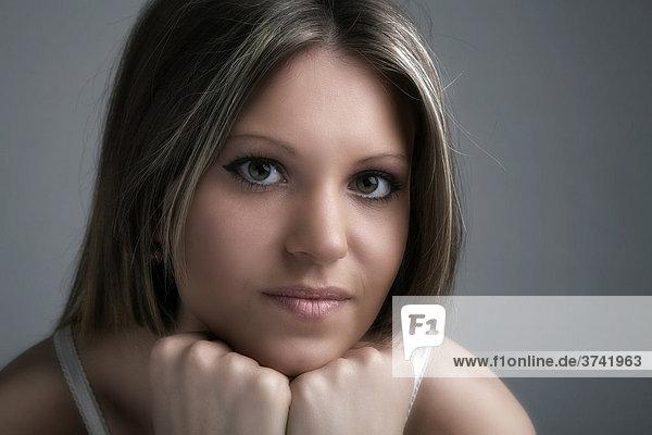 Junge Frau stützt ihr Kinn und blickt in Richtung Kamera