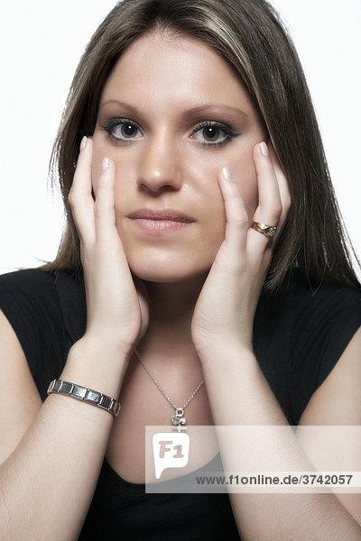 Portrait einer jungen Frau  stützt Kopf in Hände