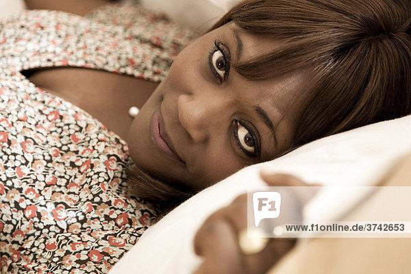 Frau  40-jährig  dunkelhäutig  liegt auf einem Kissen