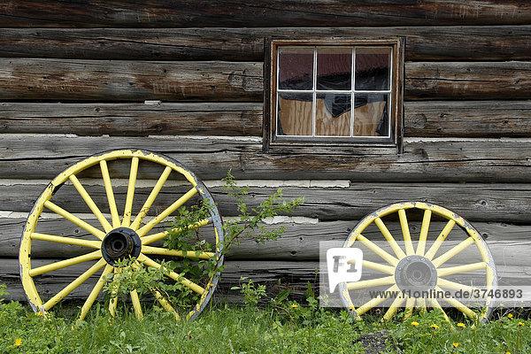 Gelbgestrichene Wagenräder vor einem Blockhaus  historisches Dorf Barkerville  British Columbia  Kanada  Nordamerika
