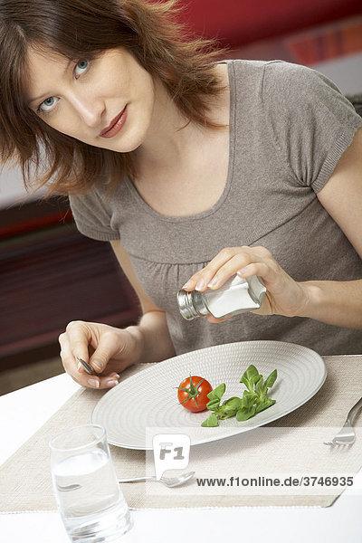 Junge Frau salzt ihren Teller