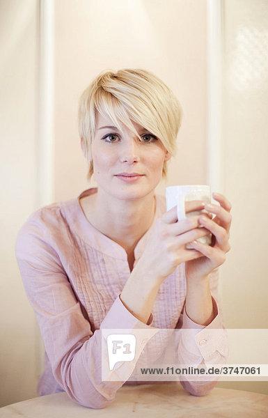 Junge Frau mit kurzen blonden Haaren trinkt Kaffee