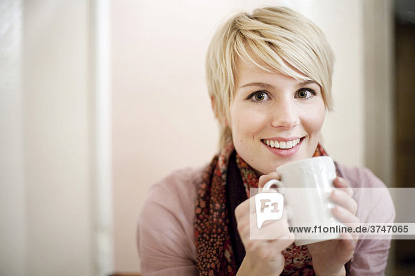 Young woman with short blonde hair drinking coffee