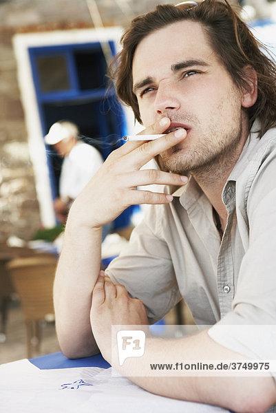 Mann raucht Zigarette im Restaurant