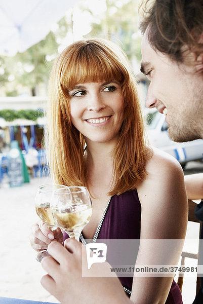 Paar klirrende Gläser mit Weißwein