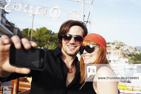 Paar beim Fotografieren vor dem Hafen