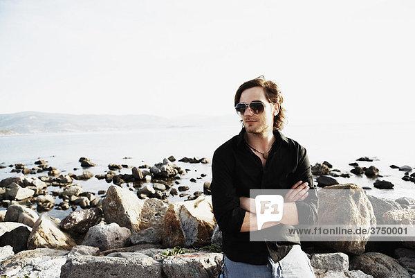 Mann sitzt vor dem Meer