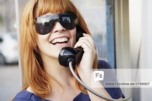 Junge Frau telefoniert an der Telefonzelle