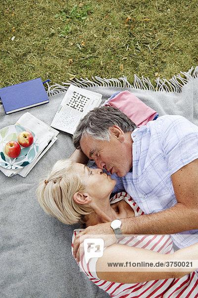 Reife Paare beim Küssen auf Picknickdecke