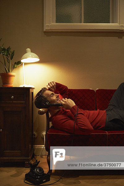 Man lying on couch phoning