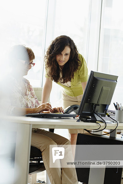 Two female colleagues working in office