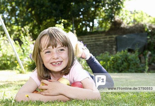 Happy girl in garden with apples